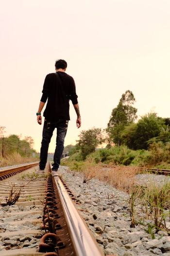 Blurry Not Focusing Alone Stone Trees Evening Relaxing Backdrop Style Twilight Outdoors Plant Dry Leaves Metal Train Back Rear Travel Railroad Track Transportation Men Road One Person People One Young Man Only