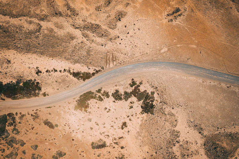 This is an aerial drone camera shot of the main road and vehicle driving during sunset. Road Path Way Dirty Field Above Aerial View Gravel Road Transportation Industry Dusty Rural Countryside Drone  Nature Dirt Track Drive Gravel Landscape Terrain Off-roading Curvy LINE Desert Arid Dry Curve Mountain Over Birdseye Remote Dangerous Surface Top Fuerteventura Volcanic  Sand Sandy Satellite Empty Land No People High Angle View