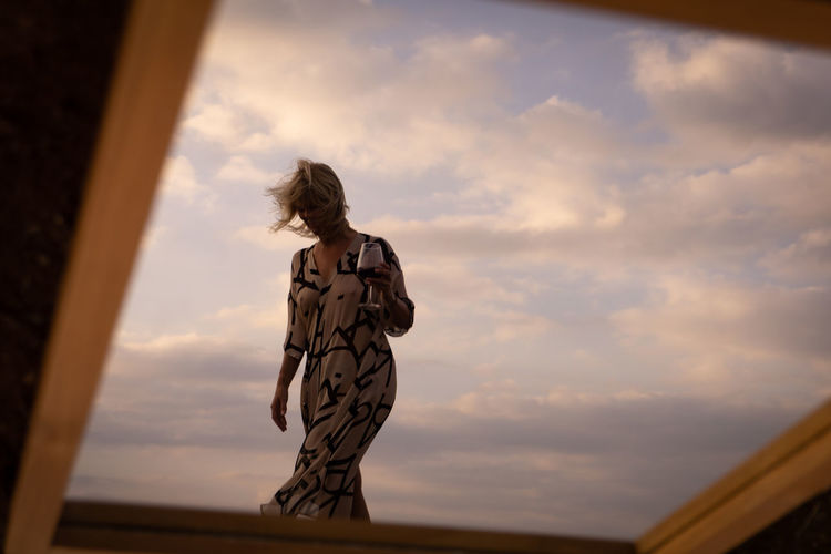 Low angle view of woman standing against sky during sunset