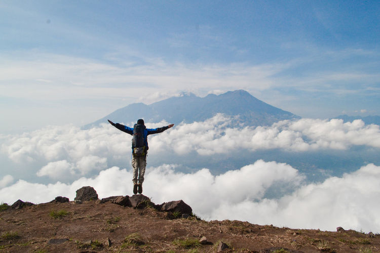 Human Arm Sky Mountain Cloud - Sky Limb One Person Standing Arms Outstretched Beauty In Nature Scenics - Nature Leisure Activity Lifestyles Real People Tranquility Rock Tranquil Scene Arms Raised Rear View Rock - Object Vacations Mountain Range Freedom Outdoors Mountain Peak Human Limb