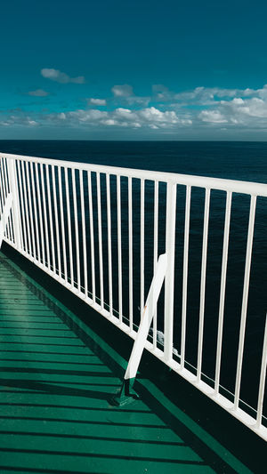 Railing by sea against blue sky