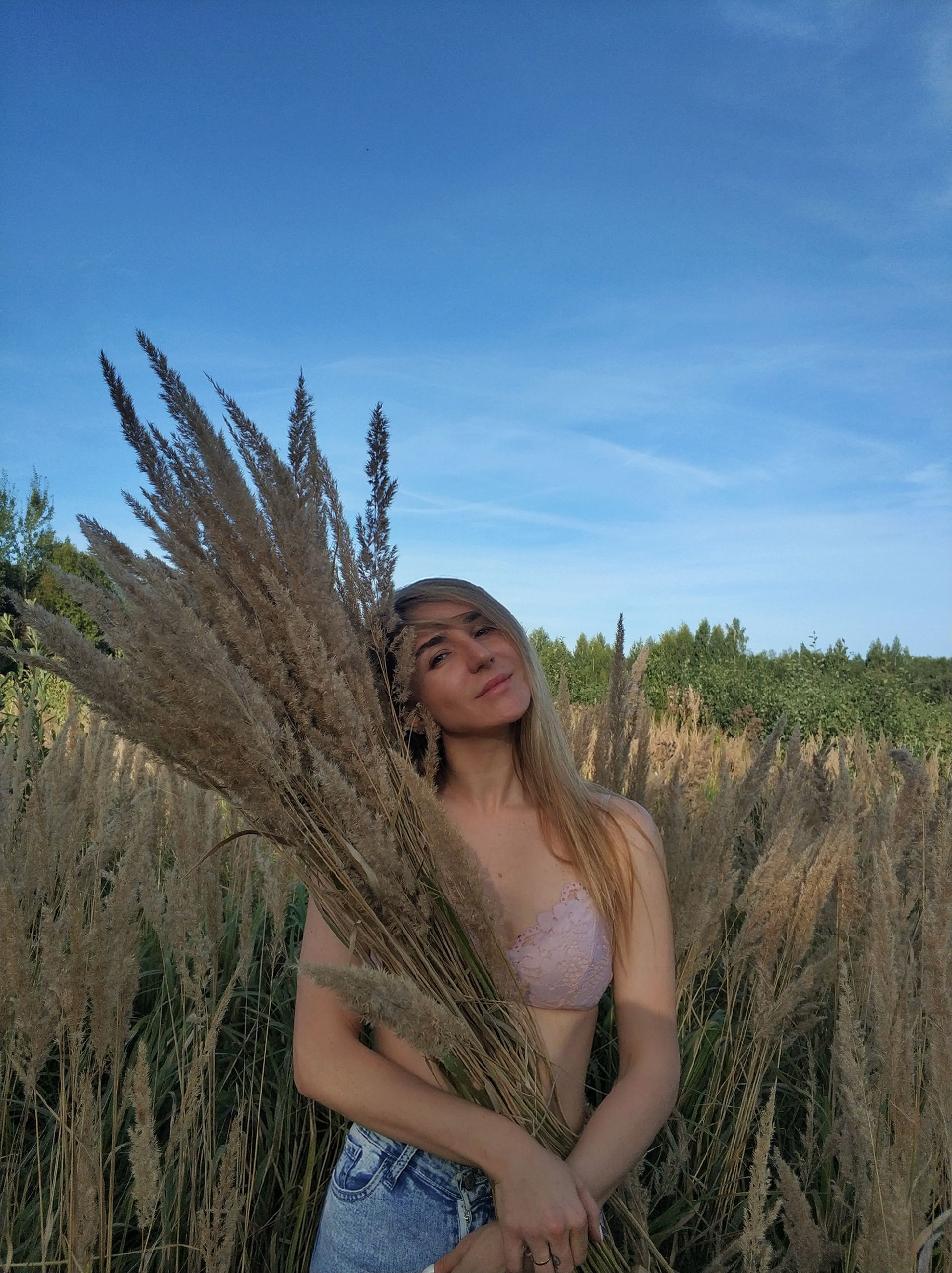 plant, sky, one person, young adult, young women, leisure activity, real people, lifestyles, field, standing, nature, land, day, growth, front view, casual clothing, three quarter length, smiling, beautiful woman, hairstyle, hair, outdoors