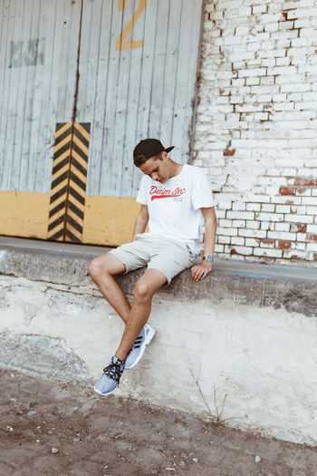 Young man sitting on wall