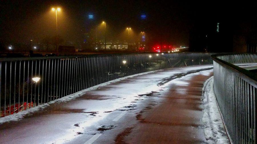 Road passing through illuminated city at night