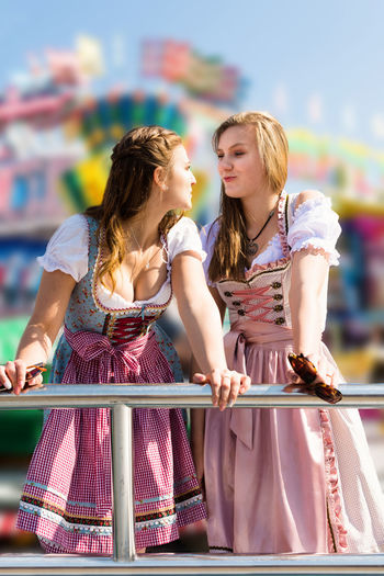 Young Female Friends Standing At Amusement Park