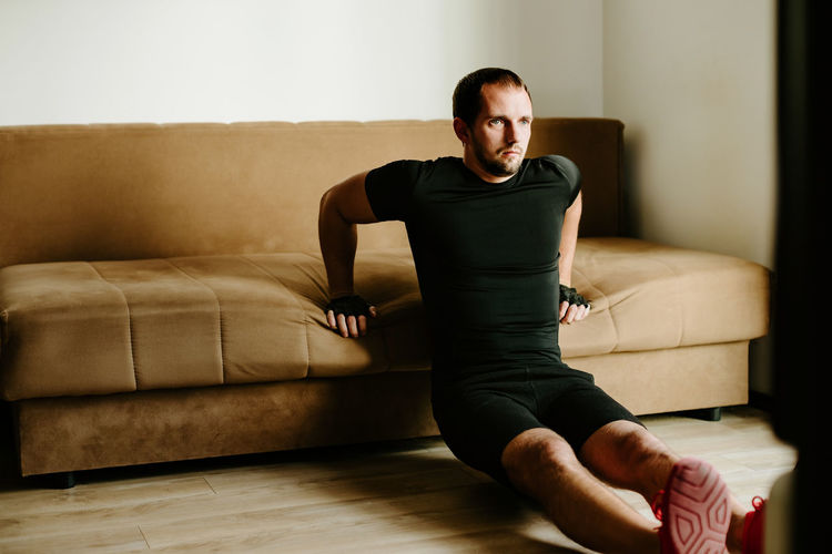 Man exercising against sofa at home