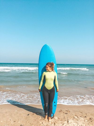 Woman with surfboard standing at beach against clear sky