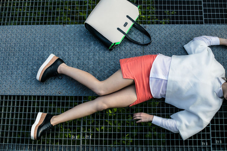 Low section of woman lying on mobile phone