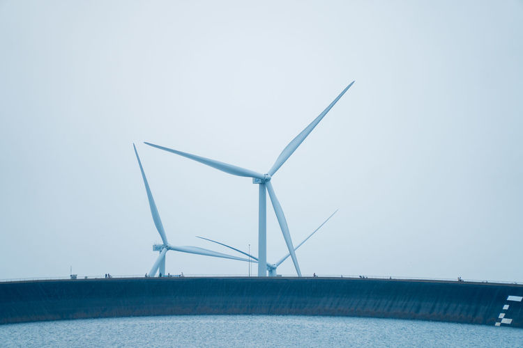 Low angle view of wind turbines by sea against clear sky