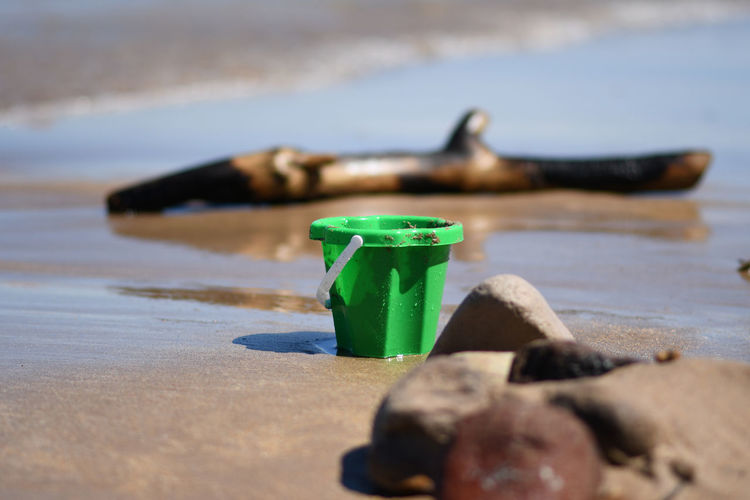 Beach Beachphotography Bucket Close-up Container Day Driftwood Equipment Focus On Foreground Green Color Land Nature No People Outdoors Plastic Sand Sea Selective Focus Shadow Still Life Summer Sunlight Surface Level Water