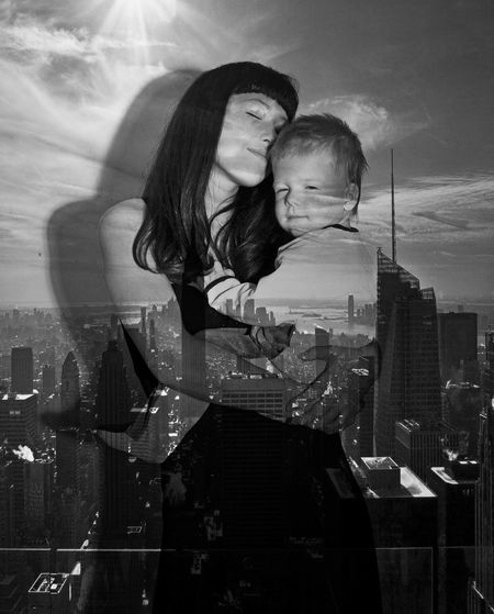 Double exposure of loving mother and son with cityscape