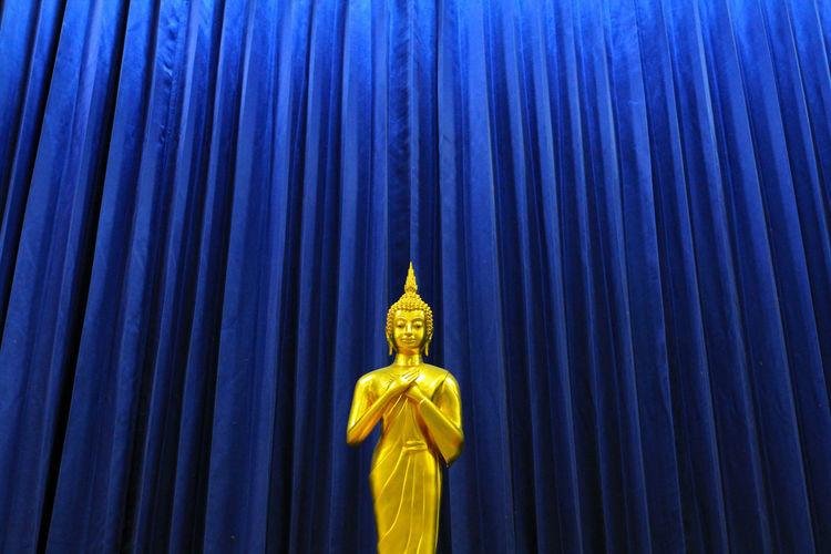 Statue of buddha against blue sky