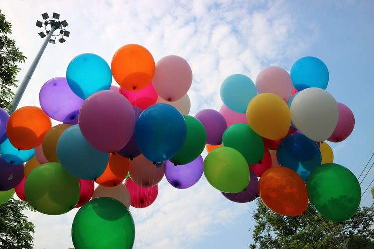 Low Angle View Of Colorful Helium Balloons Against Sky