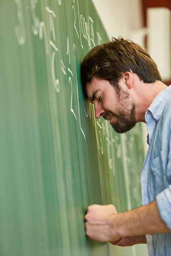 Side view of stressed student standing by blackboard in classroom
