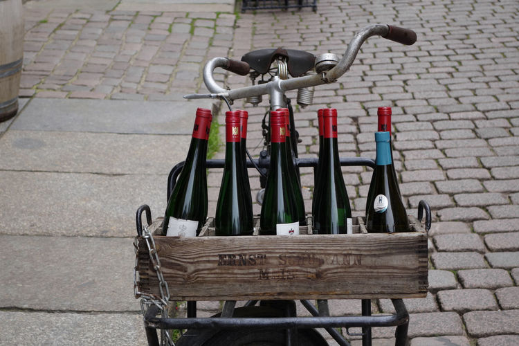 Bicycle with wine bottles for advertise Footpath Street City Day No People Bicycle Transportation Cobblestone Paving Stone Outdoors Sidewalk Absence Land Vehicle Seat Empty Container Stationary Nature Wall Wine Bottle Wine Wine Area
