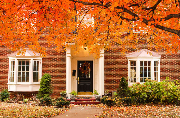 Red brick house entrance with seasonal wreath on door and porch and bay windows An autumn day with leaves on the ground and hydrageas still in bloom - colorful foliage Entrance Falling Leaves Garen Oklahoma Porch Porche Autumn Bay Windows Brick Building Exterior Curb Appeal Estate Insurance Investment Neighborhood Orange Color Pillars Property Rake Leaves Real Estate Tree Tulsa Vintage Wreath Yard Service