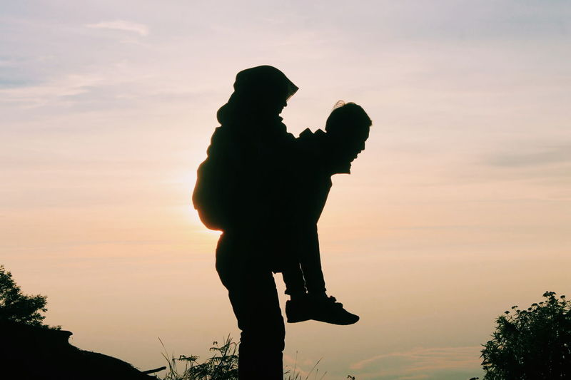 Silhouette father carrying daughter against sky during sunset