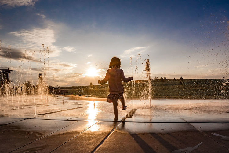 Rear view of woman standing by fountain against sky during sunset