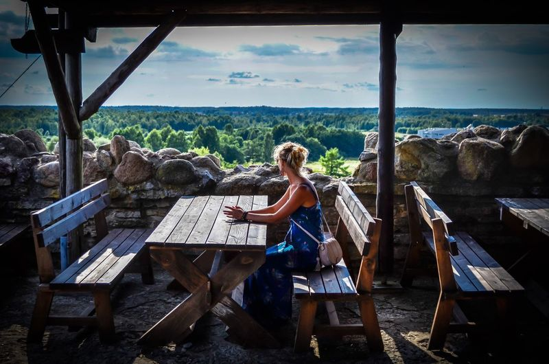 Side view of woman looking at forest while sitting at restaurant
