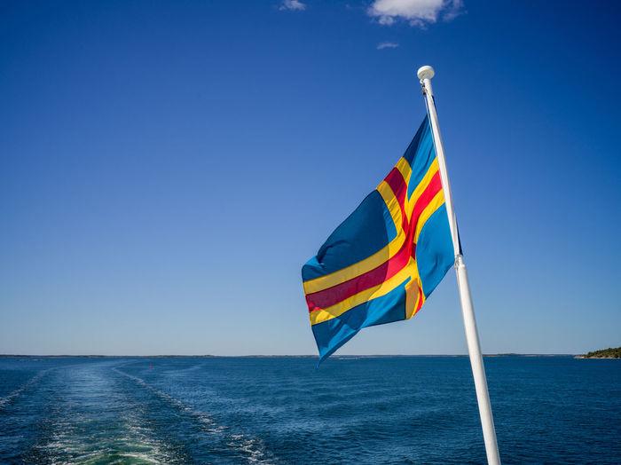 Flag flags on sea against clear blue sky