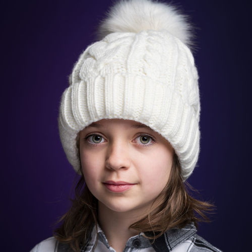 Portrait of smiling girl wearing knit hat against purple background