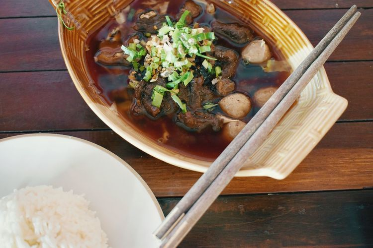 Chinese style beef soup with meatball and jasmine rice. Meat Balls EyeEmNewHere Jasmin Rice Steam Rice Wooden Table EyeEm Selects Wooden Spoon Homemade Chopsticks Bowl Table Plate Comfort Food Appetizer Wood - Material Directly Above Soup Bowl Soup Serving Dish Stew Gravy Chinese Food