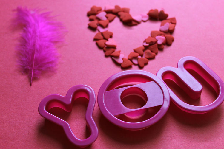 Close-Up Of Pink Pastry Cutters By Heart Shape And Feather On Table