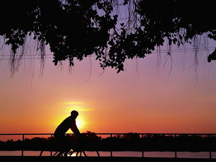 Silhouette Man Cycling By Railing Against Sky During Sunset