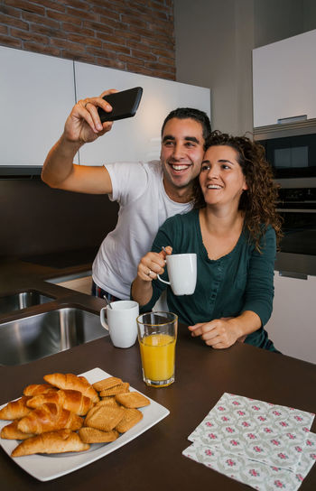Couple having breakfast in the kitchen while taking selfie Vertical Photo Biscuits Happy Phone Cell Smartphone Morning Enjoying Croissant Orange Juice  Coffee Indoor Real Two Young Woman Wife Smiling People Napkins Laughing Taking  Married Man Male Love Looking Lifestyle Husband Cheerful Caucasian Home Girl Funny Fun Female Entertainment Mobile Together Joy Social Network Selfie Kitchen Breakfast Pajama Couple