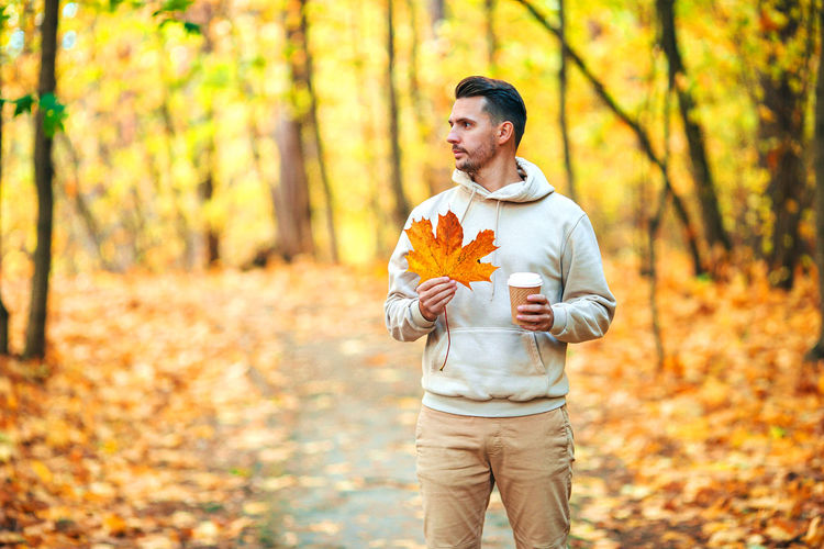 Full length of man standing in forest during autumn