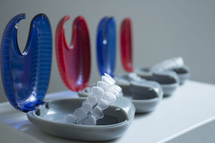 Close-up of plastic dentures in boxes on table