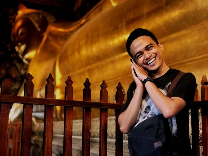 Portrait of smiling young man against buddha temple