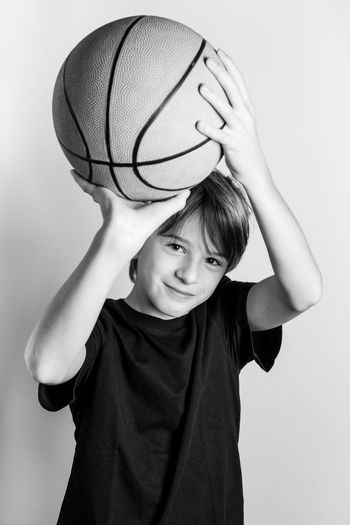 Portrait Of Smiling Teenage Boy Playing With Ball Against White Background
