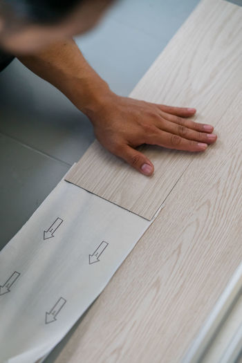 Cropped hand of carpenter on plank