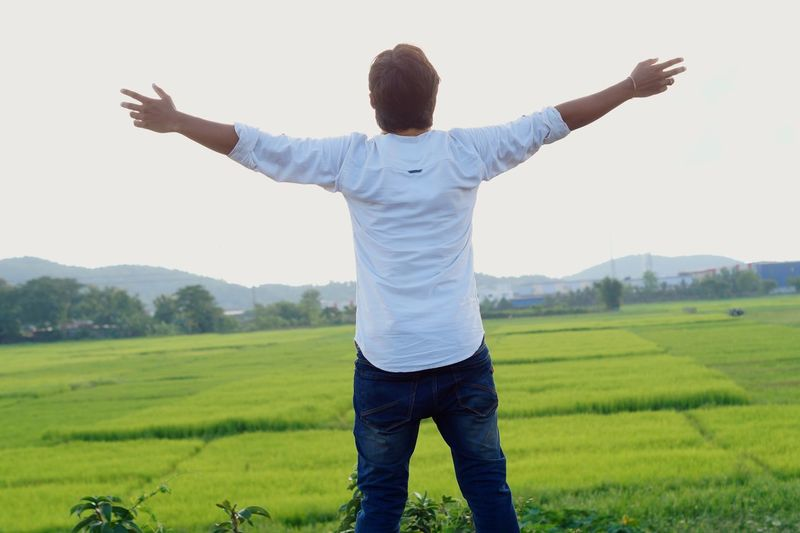Limb Human Arm One Person Landscape Rear View Human Limb Men Sky Body Part Environment Field Standing Casual Clothing Emotion Green Color Adult Human Body Part Arms Outstretched Nature Rural Scene