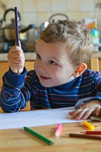 Cute boy holding colored pencil at table