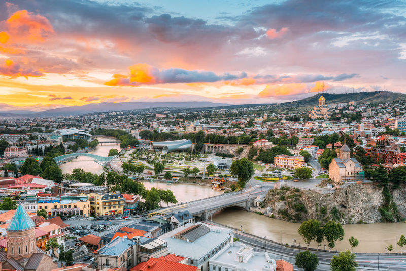 Evening View Of Tbilisi At Colorful Sunset, Georgia. Summer Cityscape. On Photograph Visible The Bridge Of Peace, A New Concert Hall, Holy Trinity Cathedral Of Tbilisi, Metekhi Church Church Bridge Of Peace Bright Caucasus Colour Your Horizn Georgia Metekhi Church Tbilisi Travel Architecture Bridge Building Cityscape Cloud - Sky Concert Hall  Evening Holy Trinity Cathedral Landmark Outdoors Residential District Sky Summer Sunrise Sunset Yellow Visual Creativity The Traveler - 2018 EyeEm Awards My Best Travel Photo