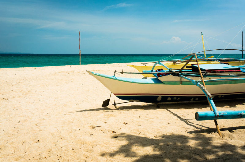 Beach Side Adventure Philippines Antique Water Nautical Vessel Sea Beach Moored Sand Shadow Blue Summer Sky Longtail Boat Pebble Beach Fishing Boat Wake Pebble Ocean Coastline Seascape Fishing Industry Horizon Over Water