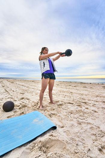 Young Woman Exercising At Beach