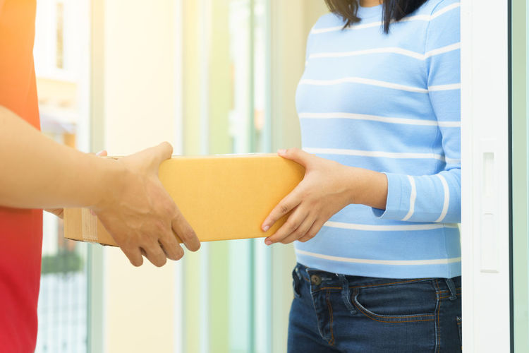 Midsection Of Woman Receiving Parcel Box From Delivery Man At Doorway