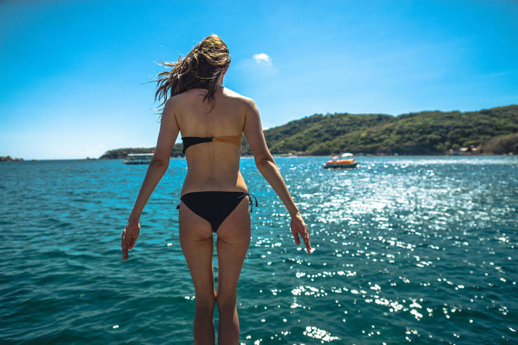 Rear View Of Young Woman By Sea Against Sky