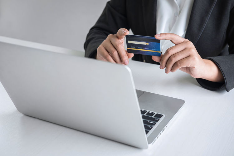 Midsection of businesswoman holding credit card by laptop on table