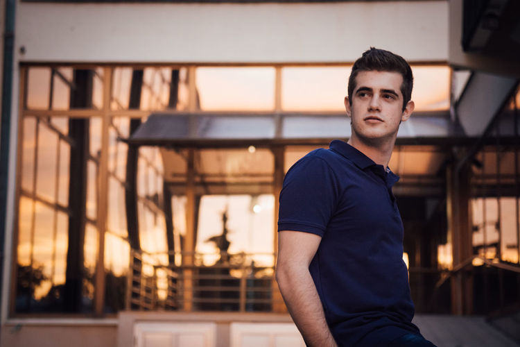 Portrait of young man standing against wall during sunset