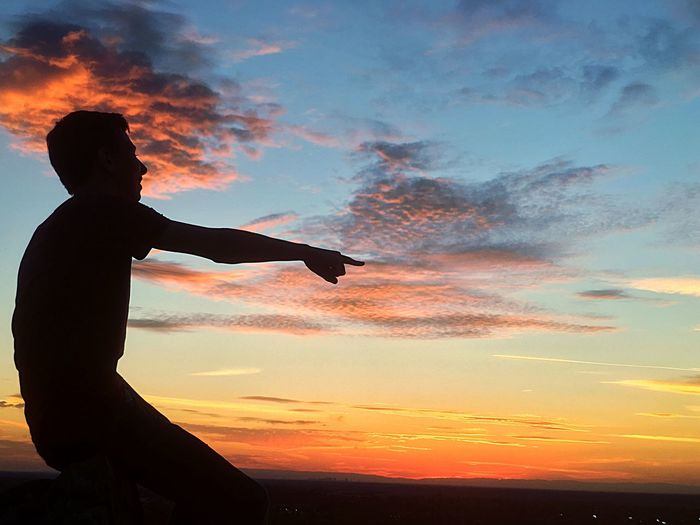 Silhouette Young Man Pointing Against Sky During Sunset