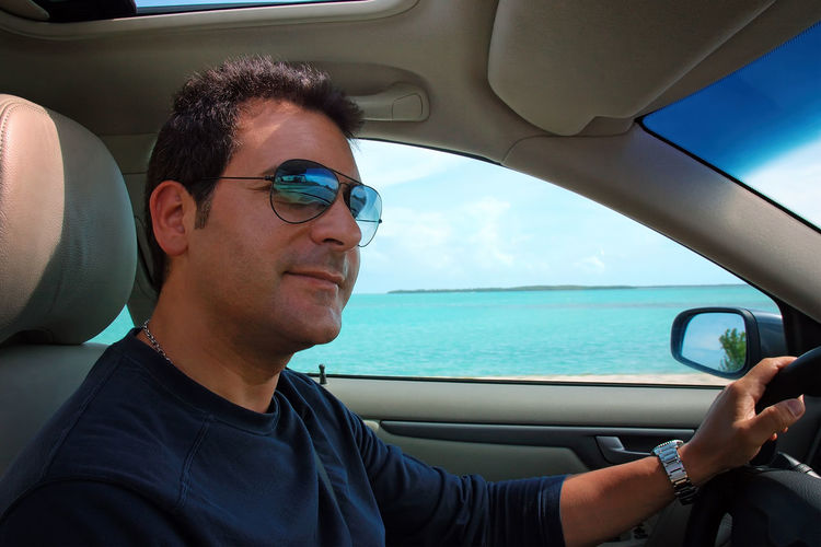 Portrait of man driving car against sea
