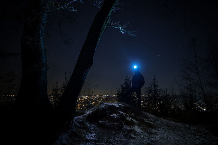 Full length of person in forest against sky at night during winter