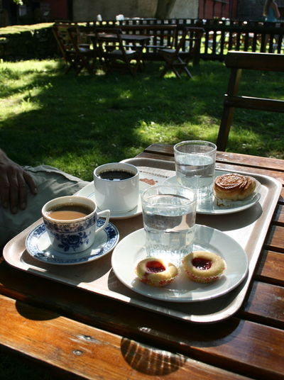 """A coffee break, called """"fika"""" in Swedish,with tradional pastry – a cinnamon bun """"kanelbulle"""" and two """"syltgrottar"""" (or """"hallongrottar""""), little cookies with raspberry (""""hallon"""") jam in the middle – at the Himmelsberga outdoor museum on Sweden's second biggest island, Öland. Swedish Lifestyle Coffee Break Shadows & Lights Glass Tray Fika Outdoor Museum Day Himmelsberga Swedish Pastry Cinnamon Bun Kanelbulle Syltgrotta Coffee - Drink Outdoors Drinking Glass Food Coffee Cup Coffee Mug Cup Drink Table Food And Drink Swedish Fika"""