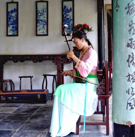 One Person Young Adult Full Length Lifestyles Beautiful Woman Young Women Real People Sitting Indoors  Day Adult People Adults Only Playing Music Chinese Musi Chinese Music Instruments Music Instruments Traditional Instruments Traditional Clothing Traditional China Chinese Young Woman Playing A Chinese Instrument