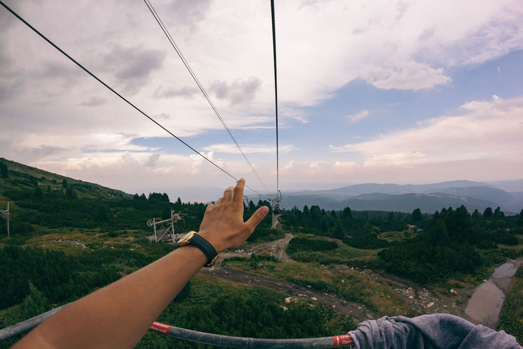 Low angle view of hand holding mountain against sky