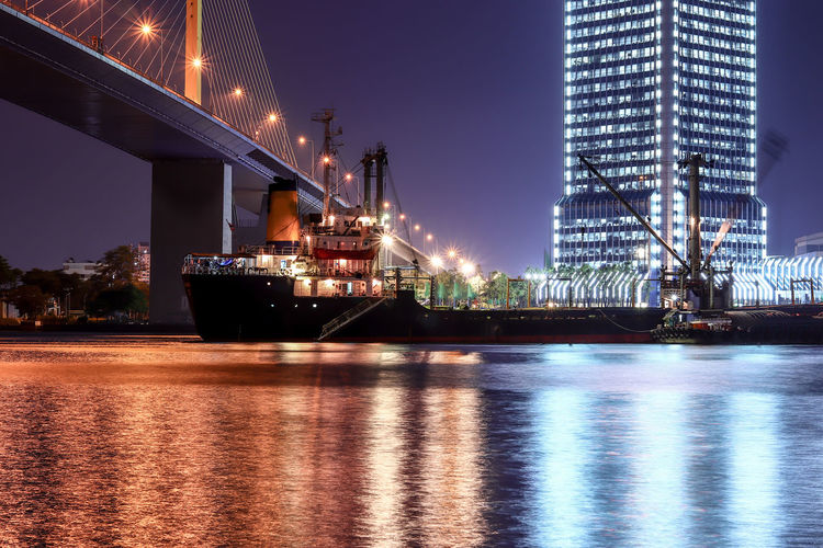 Night Cityscape Cargo Ship in River and Bridge At Bangkok Water Night Illuminated Architecture Reflection Transportation Building Exterior River Waterfront Built Structure Nautical Vessel No People Travel Destinations Nature Sky Bridge Industry Business City Bridge - Man Made Structure Outdoors Office Building Exterior Light Skyscraper Copy Space